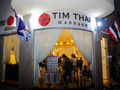 Tim Thai Massage outside view at night with people waiting in line